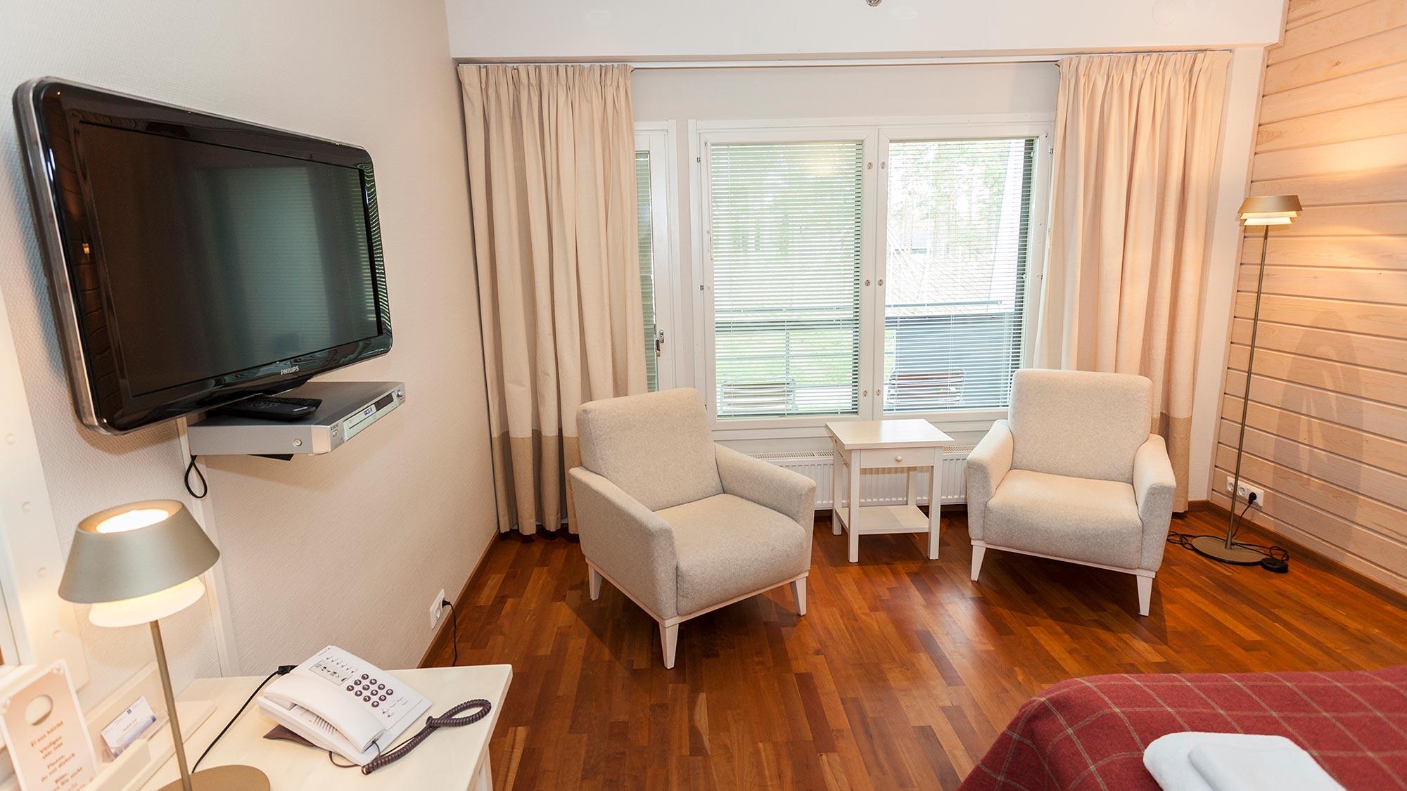 Lämpimin sävyin sisustettu Standard hotellihuone tarjoaa oman saunan rentoutumiseen.
