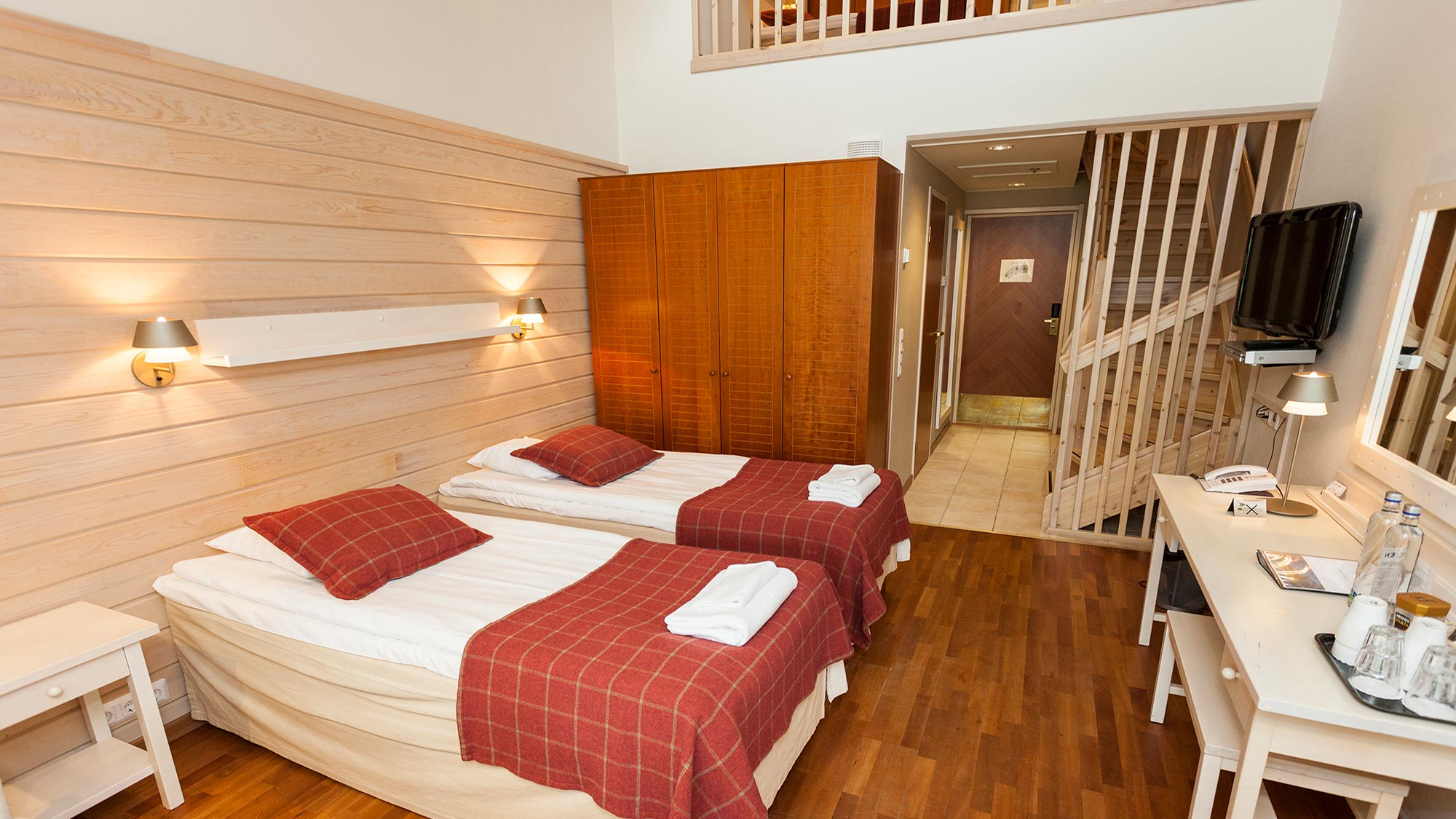 Lämpimin sävyin sisustettu Superior hotellihuone Hotel K5 Levillä majoittaa neljä vierasta kahdessa kerroksessa.