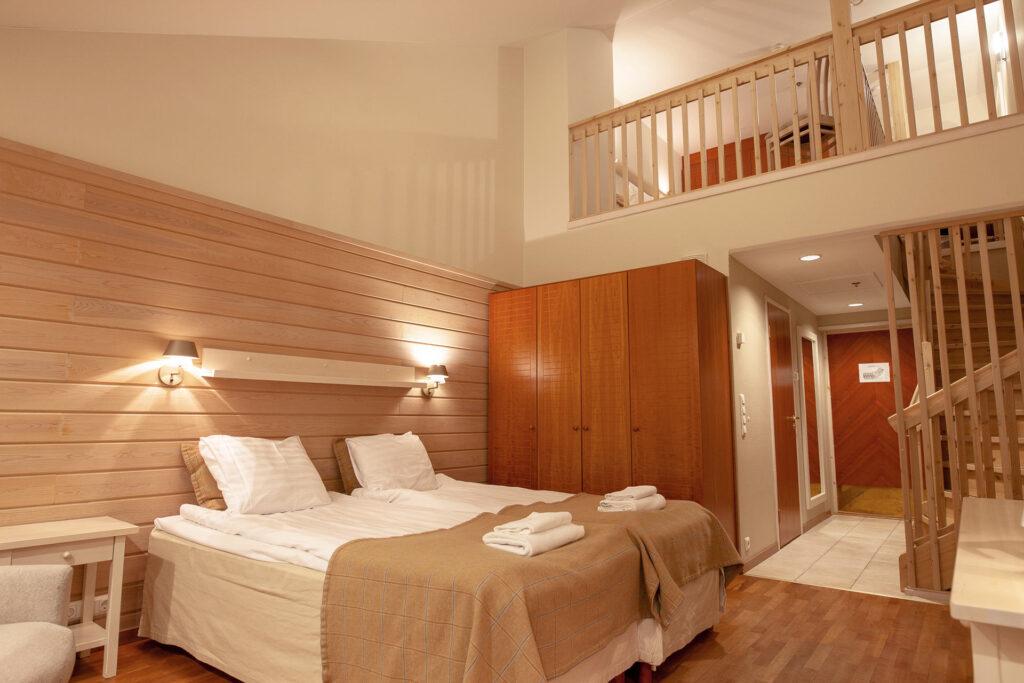 Rauhallisin sävyin sisustettu Superior hotellihuone Hotel K5 Levillä majoittaa neljä vierasta kahdessa kerroksessa.