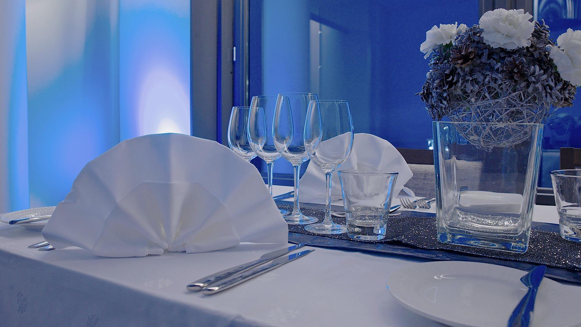 Sinisin sävyin valaistu juhlapöytä yksityistilaisuudessa Bistro K5 Levillä.